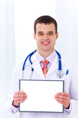 Male doctor in  white coat shows  blank tablet photo