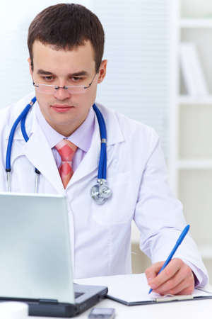 young male doctor working at a table with a laptop photo