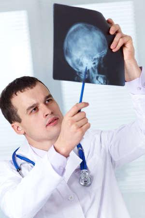 cranium: Male doctor examines  X-ray picture of a human cranium Stock Photo