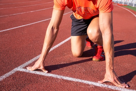 pista de atletismo: atleta musculoso joven est� en el comienzo de la cinta de correr en el estadio Foto de archivo