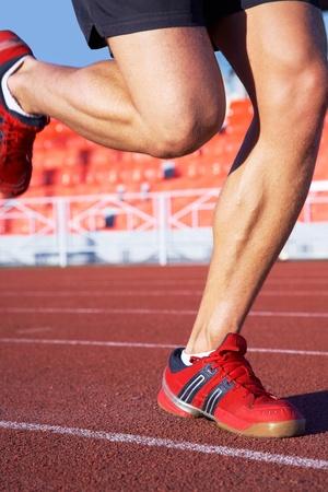 piernas hombre: las piernas de deportista que se ejecutan en el estadio. irreconocible Foto de archivo