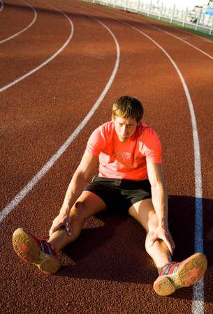 legs spread: joven atleta se sienta en las piernas del estadio rodante repartidas. El incumplimiento. Foto de archivo
