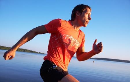 hombre deportista: Hombre joven que recorre la orilla del mar al atardecer