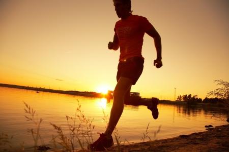 atleta corriendo: Hombre joven que recorre la orilla del mar al atardecer