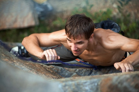 climbing sport: Photo of young man climbing up the rock