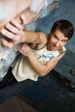 rockclimb: Young  men  climbs a semi-climbing wall Stock Photo