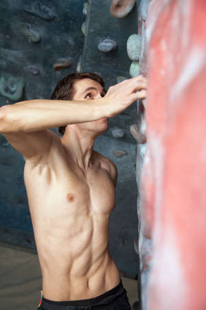 Young  men  climbs a semi-climbing wall photo
