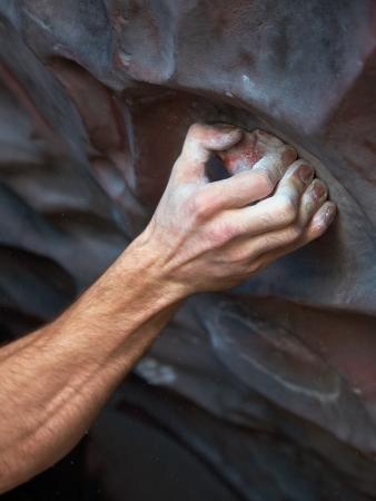 bouldering: Mano climber aggrappato saldamente alla palestra arrampicata gancio