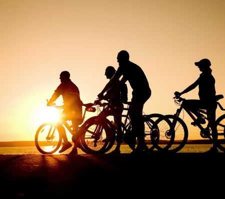 Image of sporty company teens on bicycles outdoors against sunset. Silhouette. photo