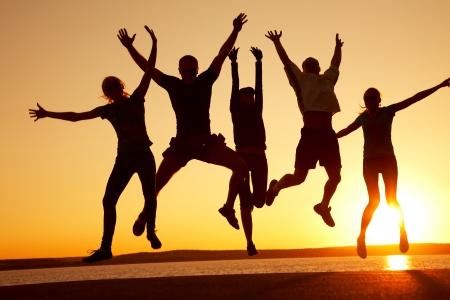 glädje: grupp lyckliga ungdomar som dansar på stranden på vackra sommar solnedgång Stockfoto