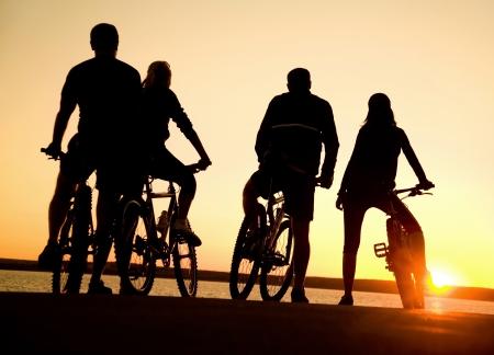 montando bicicleta: Imagen de los amigos de la empresa deportiva al aire libre en bicicleta contra la puesta del sol. Silueta.