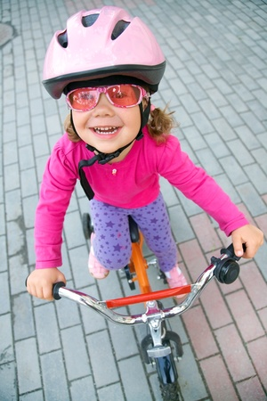 Portrait of a little girl on a bicycle in summer park outdoors photo
