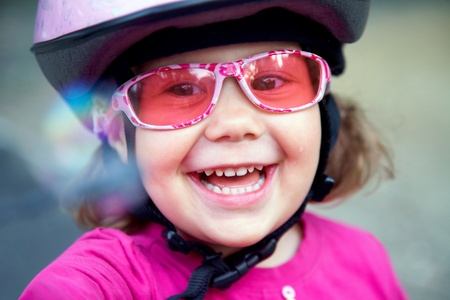 portrait of a beautiful little girl in a pink bicycle helmet and goggles photo