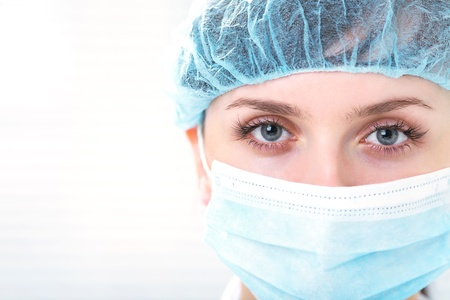 surgical care: Face of nurse in sterile mask looking at camera