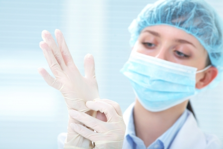 Woman doctor wearing medical gloves photo