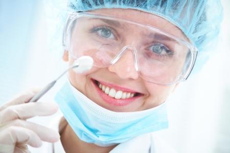 dentista: Retrato de dentista positivo sonriendo con espejo dental