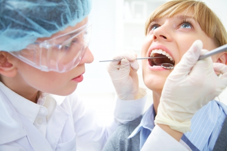 Female teeth being checked by doctor photo