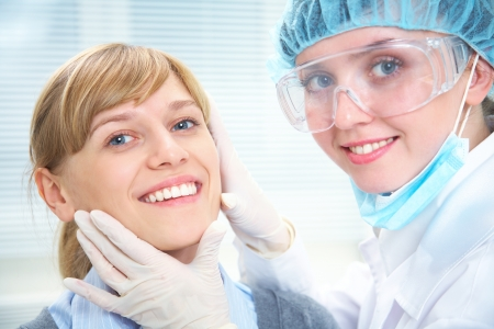 Portrait of smiling female patient  with dentist photo