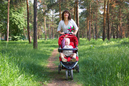 descendants: caucasian woman holding carriage with her little son in summer park background