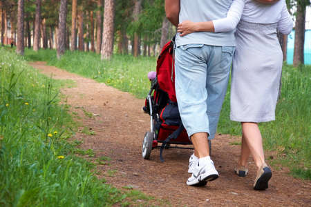 Lovely couple walking with carriage in summer park background. Back view   photo