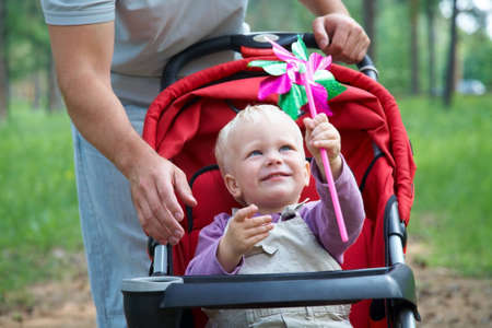Portrait of little boy in pram playing with toy in father background Stock Photo - 12838779