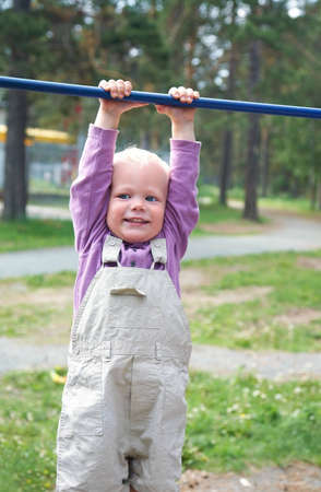 Portrait of little boy hang on horizontal bar in summer park Stock Photo - 12838766