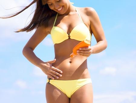 beautiful young woman in bikini smear protective cream on the skin on the beach under the sun Stock Photo - 12838820