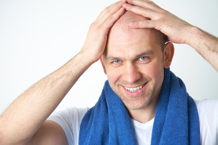 bald man: Portrait of positive bald-headed holding towel around his neck  Stock Photo