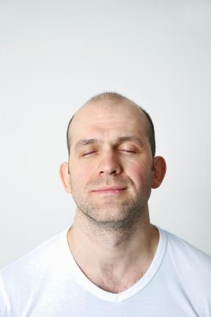 Portrait de positif homme chauve, les yeux fermés sur fond blanc