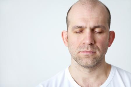 ojos cerrados: Retrato de positivo calvo sonriente sobre fondo blanco