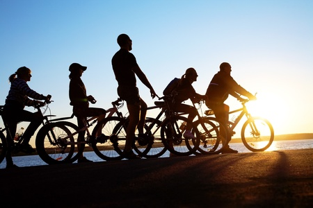 family and friends: Image of sporty company friends on bicycles outdoors against sunset. Silhouette.