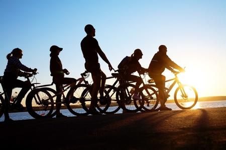 andando en bicicleta: Imagen de los amigos de la empresa deportiva al aire libre en bicicleta contra la puesta del sol. Silueta.