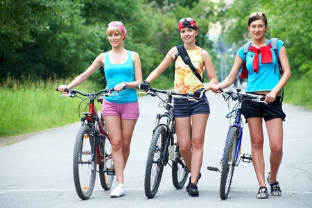 walk in: Young pretty women  walk  with  bicycle  along road in green park Stock Photo
