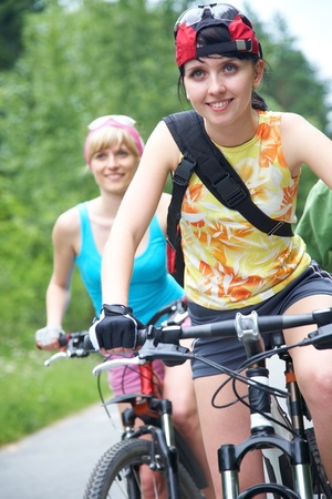 Young pretty women  ride on  bicycle  along road in green park photo