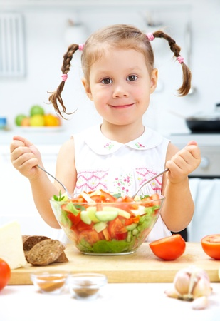 child food: Portrait of young girl preparing healthy food in the kitchen