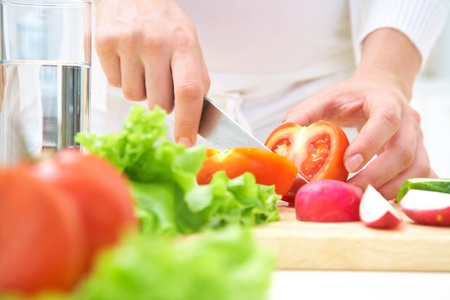 knife tomato: Human hands  cooking vegetables salad in kitchen