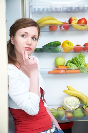 Woman looking for something in the fridge at home photo