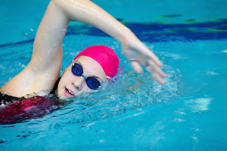 red competition: young girl swims freestyle in the pool