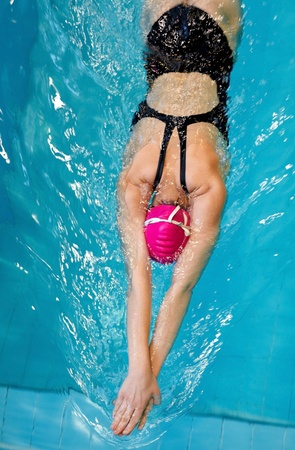 nadador: young girl swims freestyle in the pool