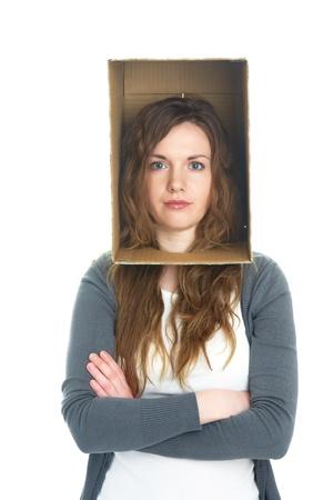 claustrophobia: conceptual portrait of a womans head hidden in a cardboard box