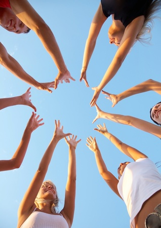 women friends: hands of young people stretching to the center