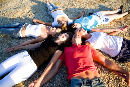 closely: group of young people lie on the beach holding hands enjoying relax