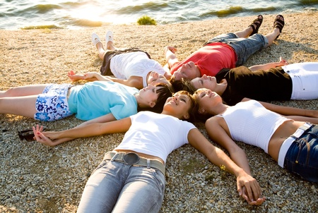 to lie: group of young people lie on the beach holding hands enjoying relax