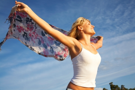 blue silk: beautiful young blond woman dancing with kerchief against the blue sky  Stock Photo