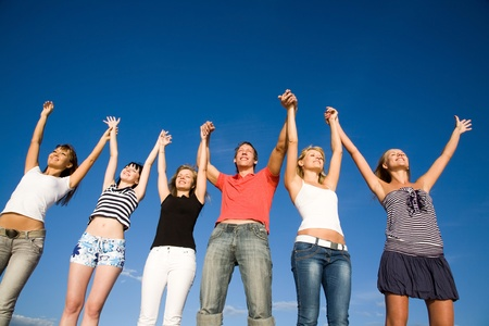 solidarity: group of happy young people holding hands raised together in the sky Stock Photo