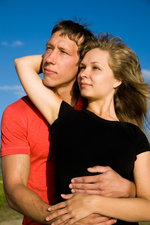 Young beautiful pair of lovers embrace background on blue sky.  Stock Photo - 12970706