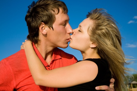 lovers kissing: Young beautiful pair of lovers kissing background on blue sky.