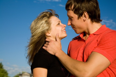lovers kissing: Young beautiful pair of lovers kissing background on blue sky. Stock Photo