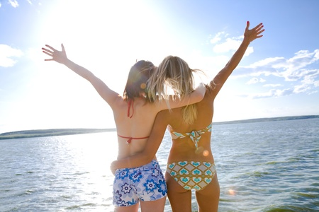 friend hug: two beautiful young girlfriends opened her hands with delight at the blue sea and sky Stock Photo