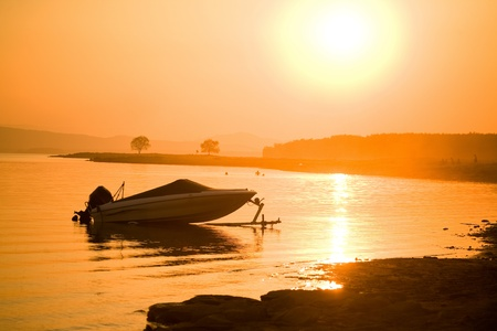 silhouette of single motor boat at sea off the coast on the background of  beautiful red sunset photo